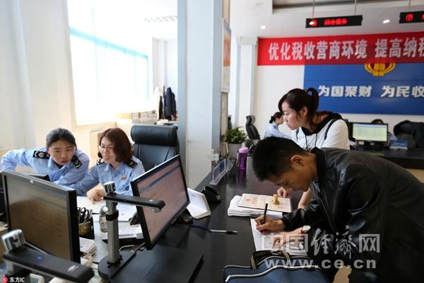 图片表明:河南省安阳市高新区国税局办税大厅,做事人员正在介绍有关事项。(图片来源:毕兴世/东方IC)